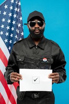 Roba di sicurezza afro-americana giovane contemporanea in uniforme nera e occhiali da sole con scheda elettorale con segno di spunta in piazza contro la bandiera degli stati uniti