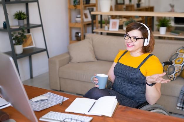 Contemporanea giovane disabile studentessa in cuffie bevendo e parlando con l'insegnante durante la lezione online davanti al computer