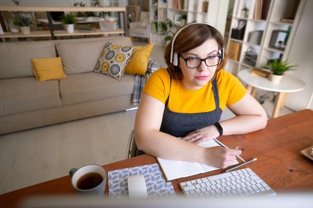 Contemporanea giovane disabile studentessa in cuffie guardando lo schermo del computer e prendere appunti durante il corso in linea