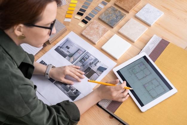 Contemporanea giovane donna designer di interni chinarsi sulla scrivania mentre guarda attraverso schizzi elettronici di appartamento nel touchpad