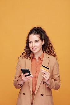 Giovane donna contemporanea con smartphone e tessera di plastica che farà ordine nel negozio online durante lo scorrimento delle merci