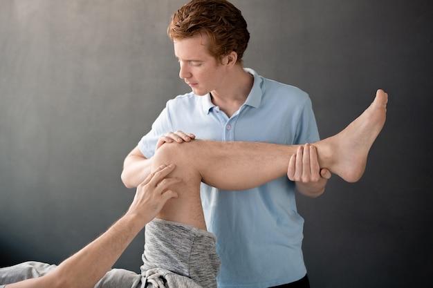 Contemporaneo giovane medico maschio che tiene la gamba piegata al ginocchio del suo paziente sdraiato sul divano durante l'esercizio fisico e lo aiuta nelle cliniche