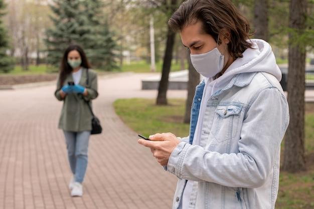 Giovane contemporaneo in maschera protettiva utilizza lo smartphone