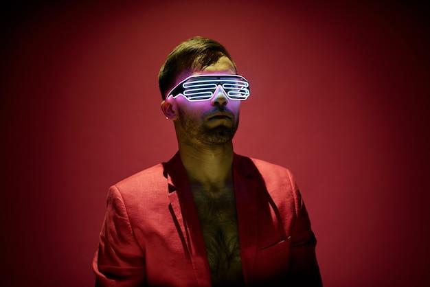 Giovane contemporaneo in giacca rossa e occhiali ad alta tecnologia in piedi nell'oscurità