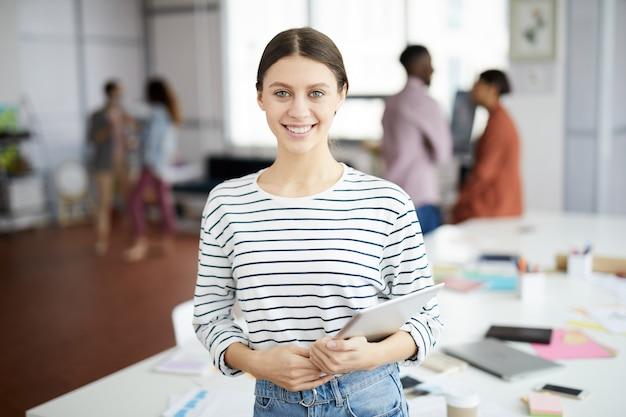 Giovane donna contemporanea che posa nell'ufficio