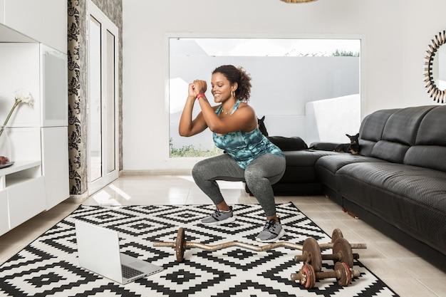 Contenuto sportivo afroamericano che fa squat mentre guarda il video tutorial online sul laptop durante l'allenamento a casa in soggiorno con i cani
