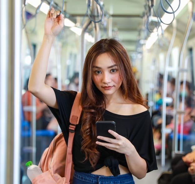 Contenuto femminile asiatico che guida il treno e chatta sui social media tramite smartphone mentre tiene il corrimano e guarda la telecamera. comunicazione e trasporto nel concetto di città.