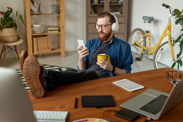 Progettista barbuto contenuto che ascolta la musica in cuffie wireless e naviga in rete mentre beve il caffè durante la pausa in ufficio