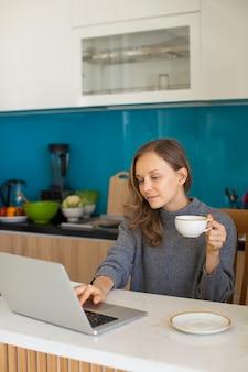 Contenuto bella signora lavorando sul portatile a casa