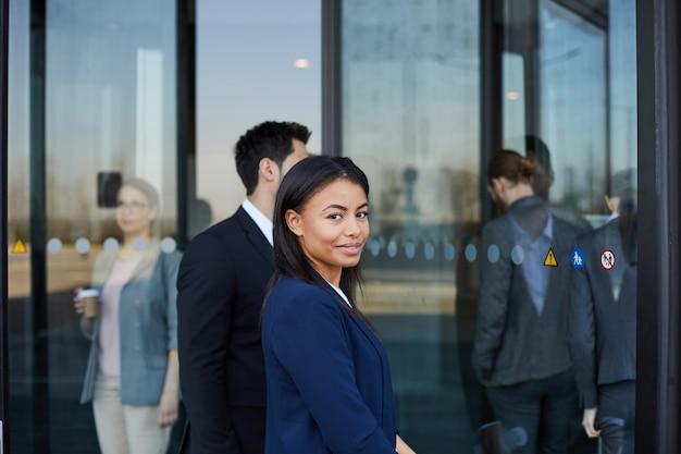 Donna di colore contenta che viene nell'edificio per uffici Foto Premium