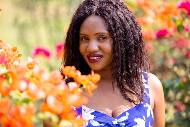 Donna nera contenta che odora di fiori nel parco.