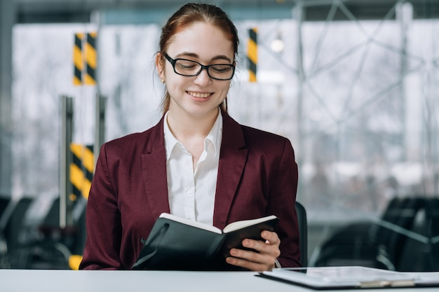 Ritratto del responsabile aziendale dei contenuti. ufficio di lavoro. giovane impiegato dell'azienda che sorride mentre guarda nel pianificatore di giorno.