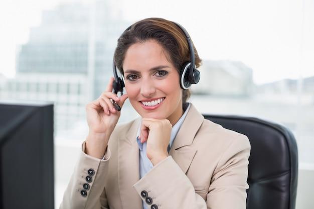 Donna di affari contentante che tocca auricolare
