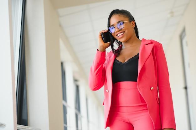 Contenuto imprenditrice camminare e parlare da smartphone. giovane donna d'affari afroamericana allegra che parla dal telefono cellulare. concetto di comunicazione