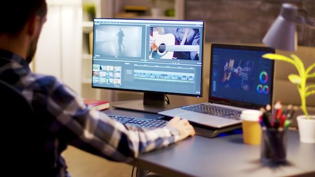 Creatore di contenuti che utilizza un software moderno per la post produzione video nell'ufficio domestico durante le ore notturne.