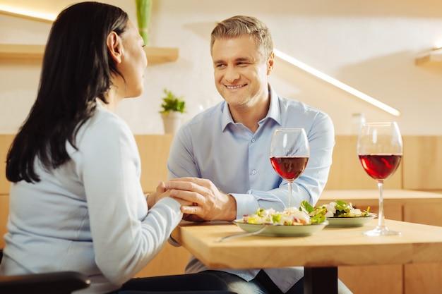 Contenuto disabile donna dai capelli scuri e un bell'uomo sorridente e ben costruito seduto in un caffè e tenendosi per mano e cenando romantico