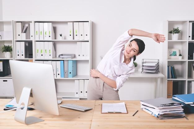 Giovane donna energica soddisfatta in camicetta che piega il lato e allunga il braccio mentre fa esercizio di riscaldamento in ufficio