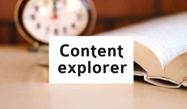 Testo del concetto di business di content explorer su un libro bianco e un orologio