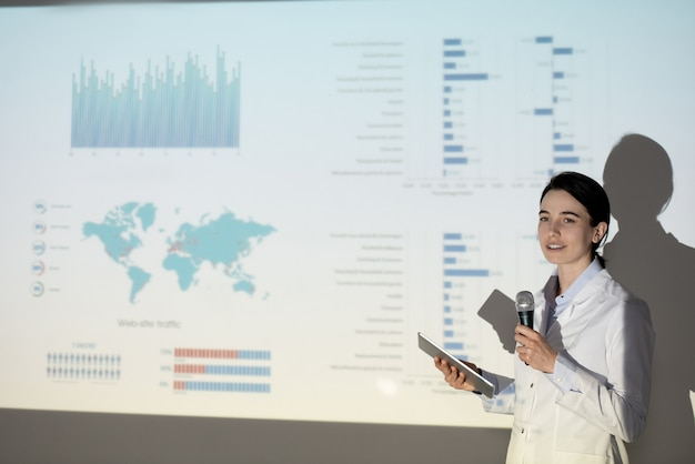 Contenuto studentessa di medicina in camice da laboratorio utilizzando tablet mentre tiene un discorso sull'infezione da coronavirus alla conferenza
