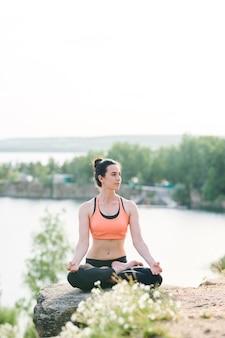Contenuti yogi femminili in reggiseno sportivo seduto nella posizione del loto e contemplando la natura mentre vi godete la meditazione all'aperto