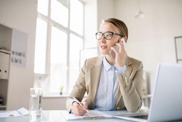 Contenuto ispirato giovane donna d'affari in giacca elegante seduto alla scrivania e prendere appunti mentre parla al telefono cellulare in ufficio