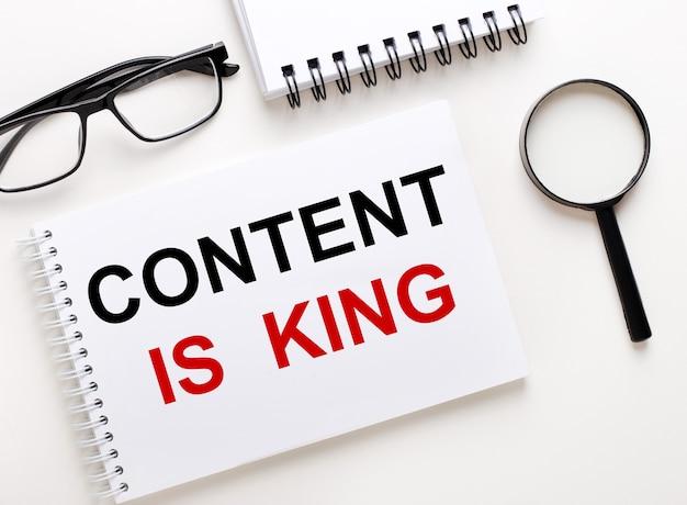 Content is king è scritto in un taccuino bianco su una parete chiara vicino al taccuino, occhiali con cornice nera e una lente d'ingrandimento.