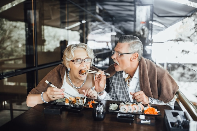 Contento uomo e donna seduti alla terrazza estiva mangiando sushi e trascorrere del tempo insieme felicemente