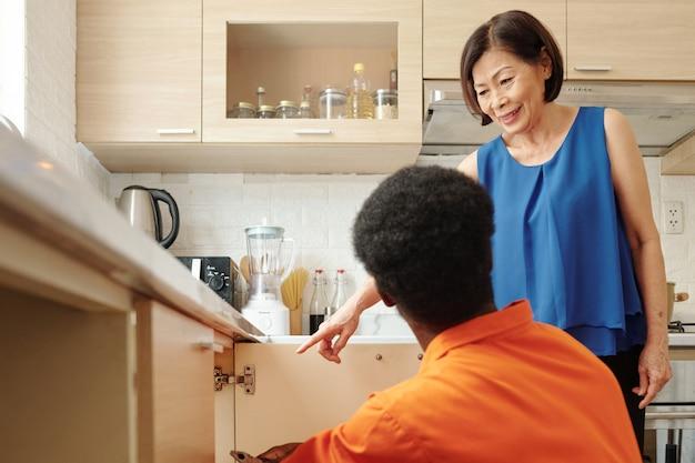 Contento proprietario di casa maturo che indica il tubo nell'armadio della cucina verso l'idraulico nero che ripara gli impianti idraulici