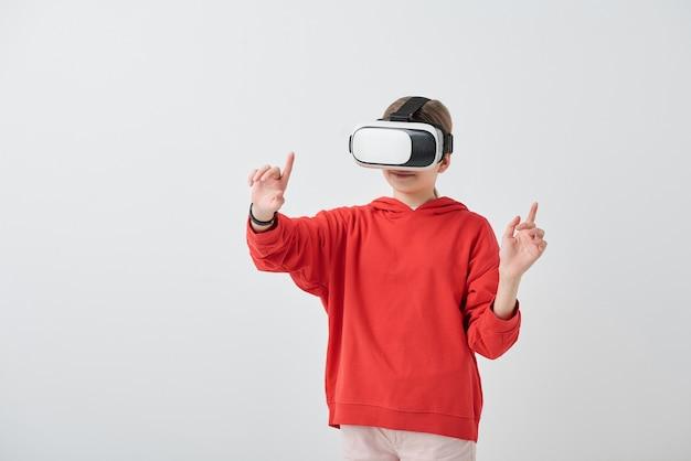 Ragazza della scuola di contenuto in felpa con cappuccio rossa che gesticola mano mentre si gode la realtà virtuale nel simulatore di vr