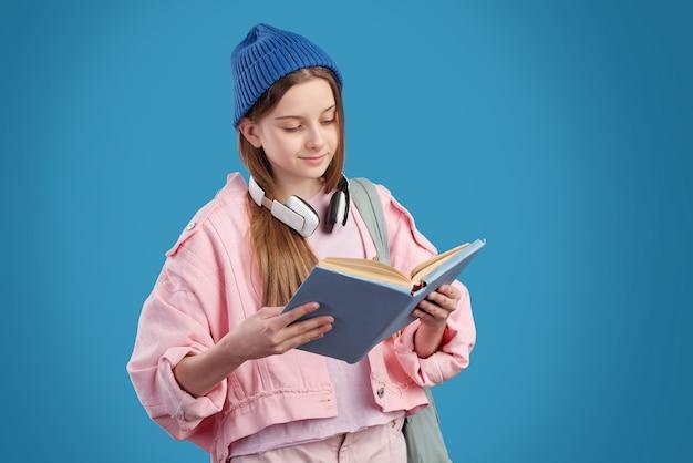 Scolara contenta con le cuffie intorno al collo in piedi e leggendo il libro di testo