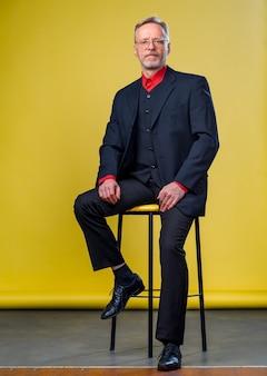 Contento uomo d'affari senior sorridente in un abito scuro. gambe alla mano. maglietta rossa. sicuro di se. concetto di stile aziendale