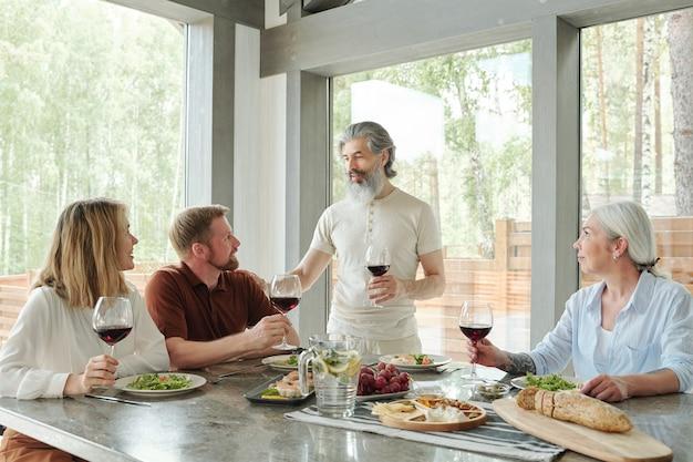 Contenuto senior padre dalla barba grigia che tiene il bicchiere di vino e che dà pane tostato alla cena in famiglia