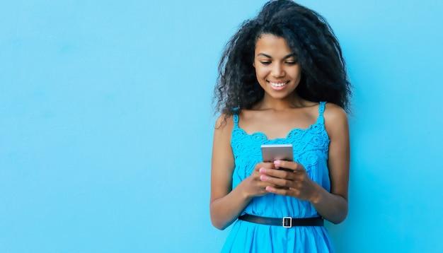 Contenta ragazza etnica africana adolescente con lunghi capelli neri come il jet sta tenendo uno smartphone in mano, sorride mentre naviga in internet o controlla il feed