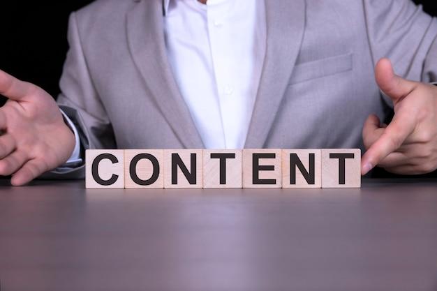 Contenuto, la parola è scritta su cubi di legno, sullo sfondo di un uomo d'affari in abito grigio.