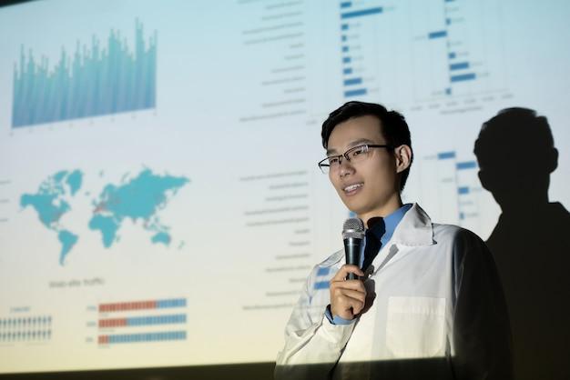 Contenuto giovane biologo asiatico in occhiali e camice da laboratorio che dà discorso contro lo schermo di proiezione con dati statistici