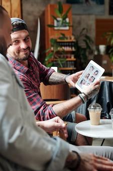 Contenuto giovane uomo barbuto che mostra le foto delle donne ad un amico mentre sceglie la ragazza tramite l'app di appuntamenti online