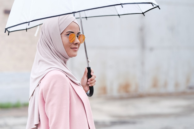 Contenta giovane donna musulmana in hijab rosa con ombrellone e occhiali da sole come protezione dal sole mentre cammina da sola o aspetta un amico