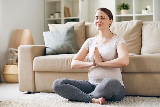 Giovane donna incinta soddisfatta che si siede con le mani in namaste e medita con gli occhi chiusi a casa