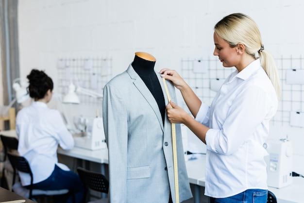 Giovane donna soddisfatta con capelli biondi che sta al manichino e misura le taglie della giacca