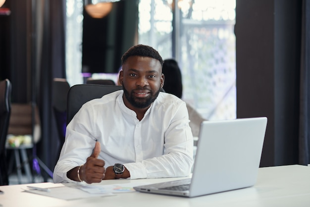 Il responsabile di ufficio afroamericano contento lavora al computer portatile che sorride e al pollice alzato.