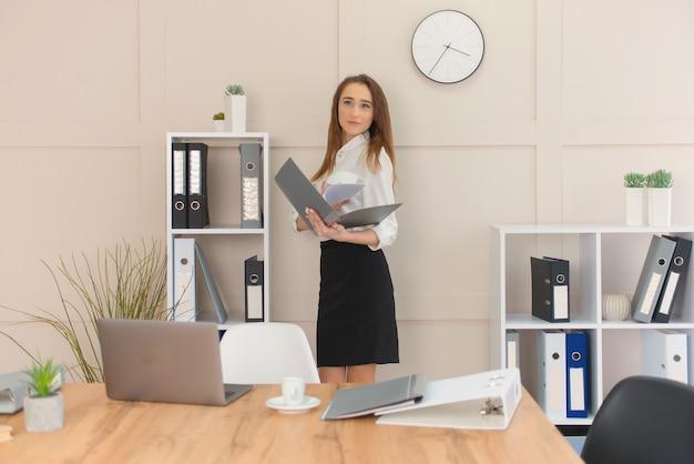 Donna di affari femminile soddisfatta che posa con i documenti in mano contro il suo ufficio minimalista.