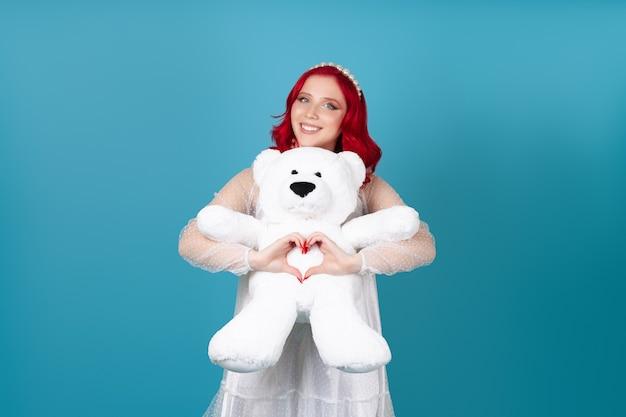 Una donna felice innamorata in un abito bianco abbraccia un orsacchiotto bianco e fa un cuore con le dita