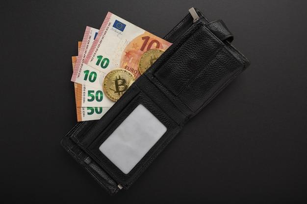 Il contenuto del portafoglio di un uomo, banconote in euro e bitcoin su fondo nero