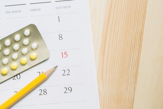 Pillole di controllo contraccettive alla data del calendario. concetto di assistenza sanitaria e medicina