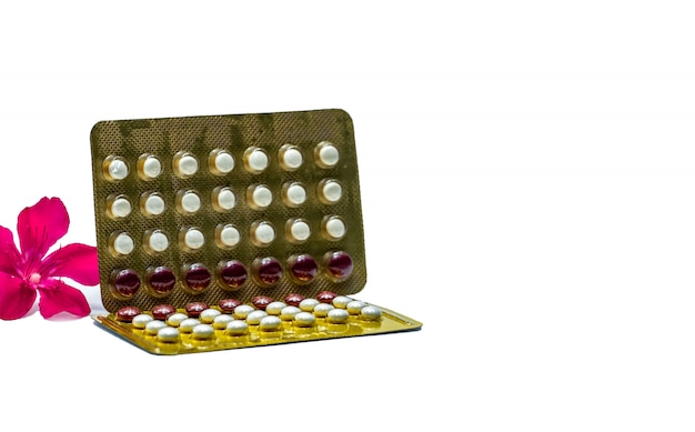 Pillole contraccettive o pillole anticoncezionali con fiore rosa su sfondo bianco con spazio di copia. concetto di pianificazione familiare. compresse ormonali rotonde bianche e rosse in blister. ormone per la contraccezione