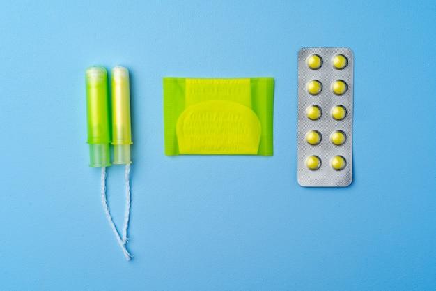Pillole contraccettive, assorbenti igienici e tamponi su sfondo blu