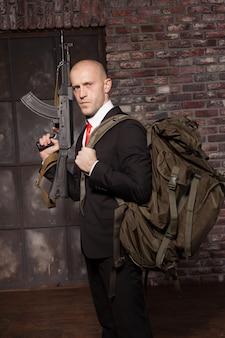 Killer a contratto pronto per la missione segreta. assassino assunto in giacca e cravatta rossa con zaino che tiene in mano la mitragliatrice.