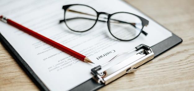 Un contratto su un tavolo da lavoro in legno con occhiali e una matita rossa. i documenti sono pronti per la firma. concetto di affari. accordo di collaborazione.
