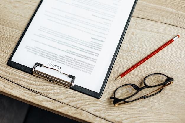Un contratto su un tavolo da lavoro in legno con occhiali e una matita rossa