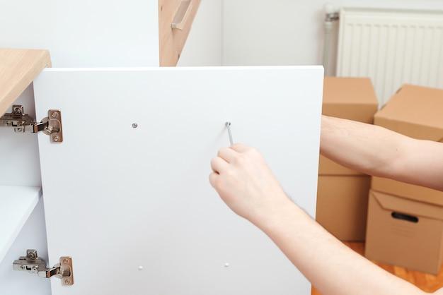 Riparatore dell'appaltatore che monta nuovi mobili in appartamento moderno.